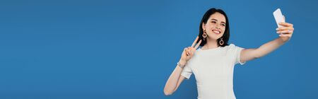 panoramic shot of smiling elegant woman in dress taking selfie and showing peace sign isolated on blue