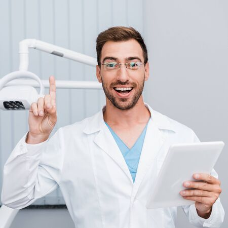 happy bearded man in white coat and glasses gesturing while holding digital tablet