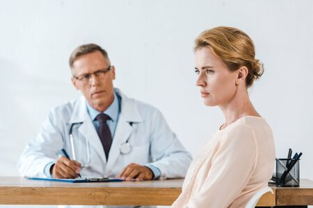 selective focus of upset woman sitting near doctor in white coat 写真素材