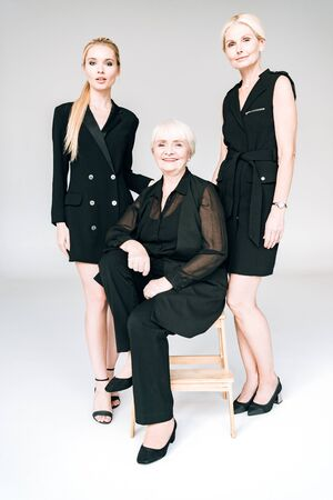 full length view of elegant three-generation blonde women in total black outfits isolated on grey 스톡 콘텐츠