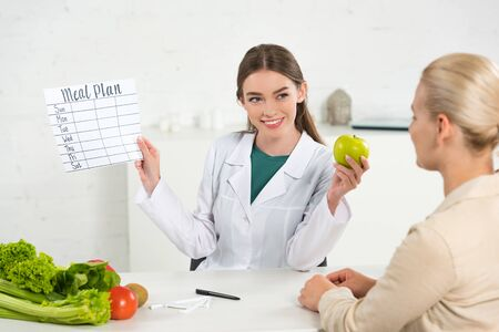 smiling dietitian in white coat holding meal plan and apple and patient at table