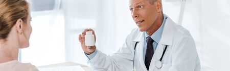 panoramic shot of doctor holding bottle and looking at patient 写真素材
