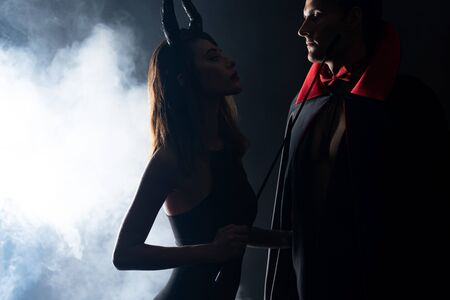 handsome man in cloak looking at girl with horns holding flogging whip on black with smoke 스톡 콘텐츠