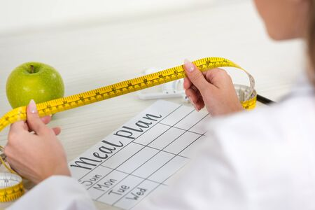 cropped view of dietitian holding measure tape at workplace 写真素材