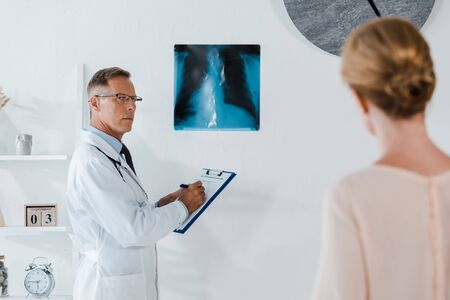 selective focus of doctor in glasses writing diagnoses on clipboard near x-ray and looking at woman in clinic 写真素材