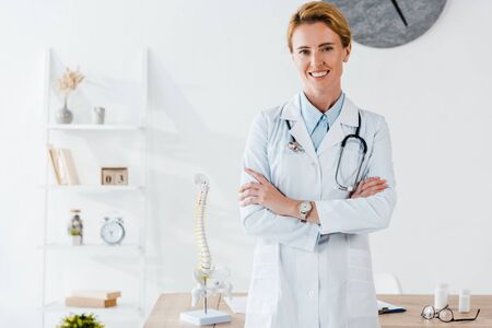 attractive and positive doctor standing with crossed arms in clinic