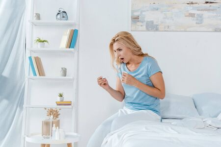 shocked woman holding digital thermometer while sitting on bed at home 写真素材