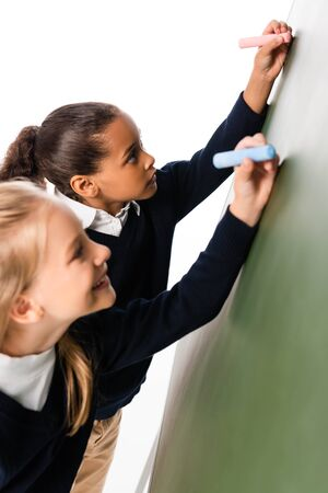two adorable multicultural schoolgirls writing on green chalkboard