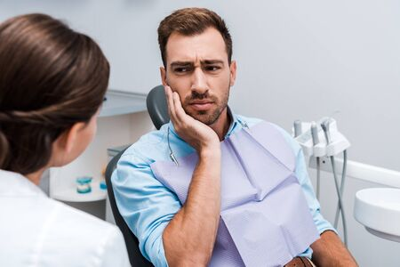 selective focus of upset patient touching face while having toothache near dentist Archivio Fotografico