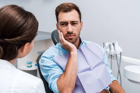 Selektiver Fokus des verärgerten Patienten, der das Gesicht berührt, während er Zahnschmerzen in der Nähe des Zahnarztes hat Standard-Bild
