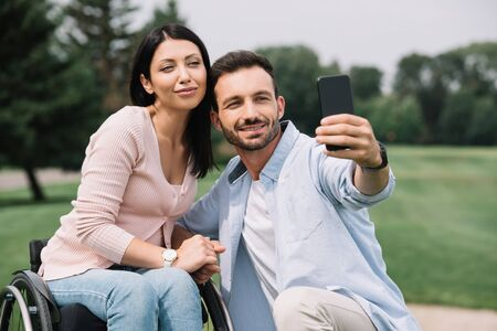 happy man taking selfie on smartphone with smiling disabled girlfriend in park