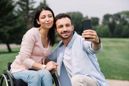 homme heureux prenant selfie sur smartphone avec petite amie handicapée souriante dans le parc