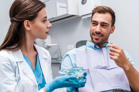 selektywne skupienie przystojnego mężczyzny trzymającego aparat w pobliżu dentysty z modelem zębów w rękach