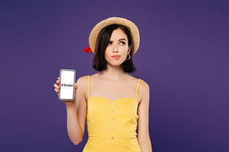 KYIV, UKRAINE - JULY 3, 2019: dreamy pretty girl in straw hat holding smartphone with tinder app isolated on purple