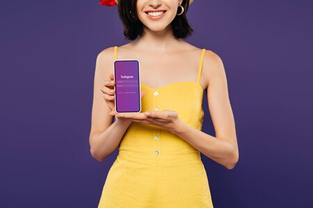 KYIV, UKRAINE - JULY 3, 2019: cropped view of smiling girl holding smartphone with instagram app isolated on purple