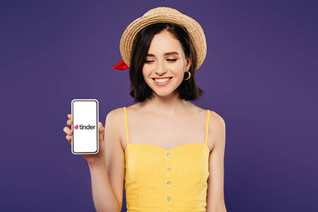 KYIV, UKRAINE - JULY 3, 2019: smiling girl in straw hat holding smartphone with tinder app isolated on purple