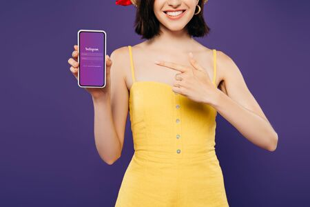KYIV, UKRAINE - JULY 3, 2019: cropped view of girl in straw hat pointing with finger at smartphone with instagram app isolated on purple