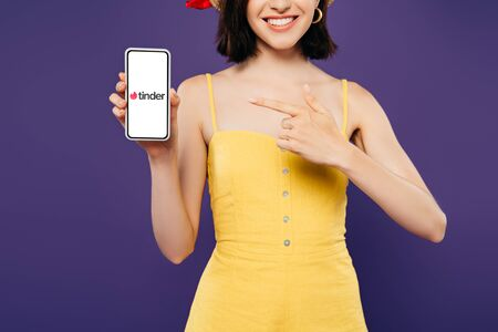 KYIV, UKRAINE - JULY 3, 2019: cropped view of girl in straw hat pointing with finger at smartphone with tinder app isolated on purple