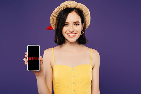 KYIV, UKRAINE - JULY 3, 2019: smiling girl in straw hat holding smartphone with netflix app isolated on purple