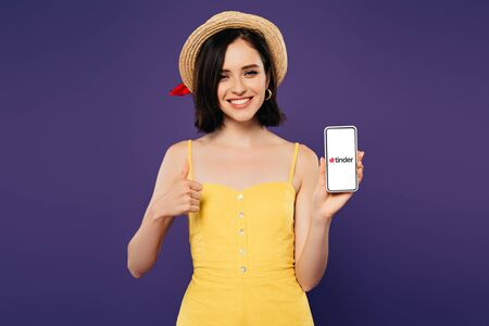 KYIV, UKRAINE - JULY 3, 2019: smiling pretty girl in straw hat showing thumb up while holding smartphone with tinder app isolated on purple Editorial