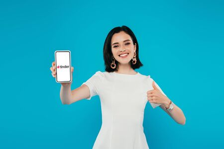 KYIV, UKRAINE - JULY 3, 2019: smiling elegant woman in dress holding smartphone with tinder logo and showing thumb up isolated on blue
