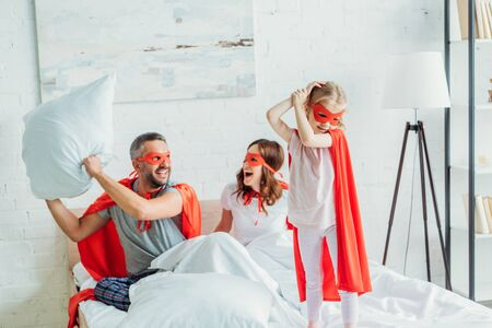 cheerful father in costume of superhero holding pillow while sitting in bed near wife and daughter