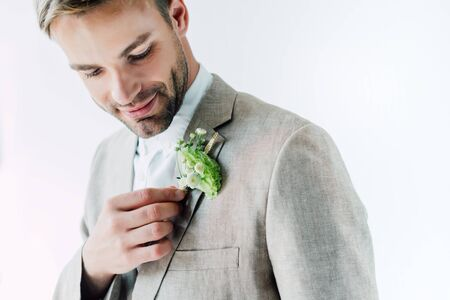 handsome bridegroom in suit holding floral boutonniere and looking at it isolated on grey