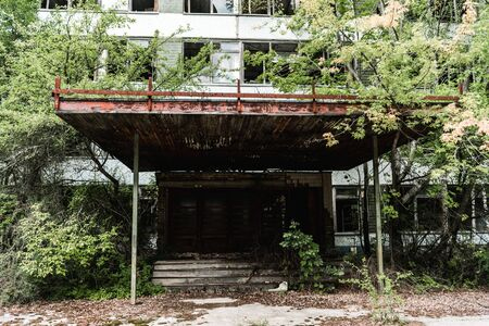 abandoned building near green trees with leaves in chernobyl 写真素材