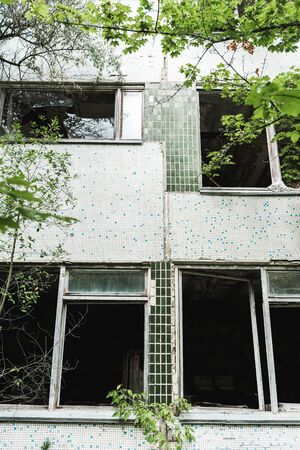 selective focus of abandoned building near green trees in chernobyl