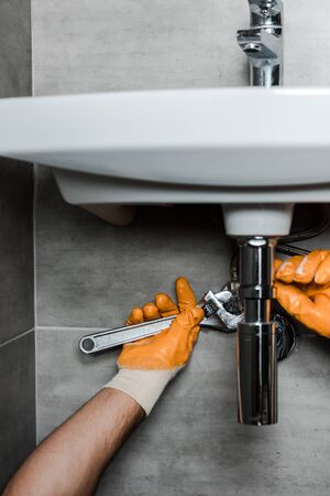 cropped view of repairman in rubber gloves fixing water damage with adjustable wrench