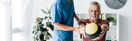 panoramic shot of mature man training with ball near doctor