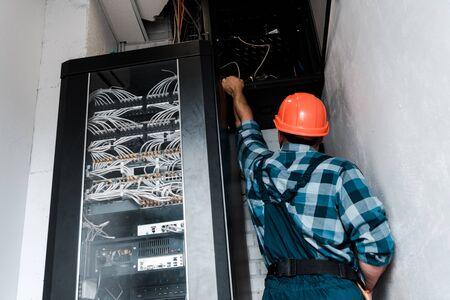 Rückansicht des Technikers im Schutzhelm, der Drähte und Kabel berührt