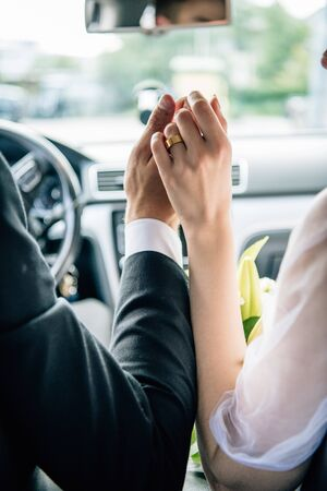 cropped view of bridegroom and bride holding hands in car