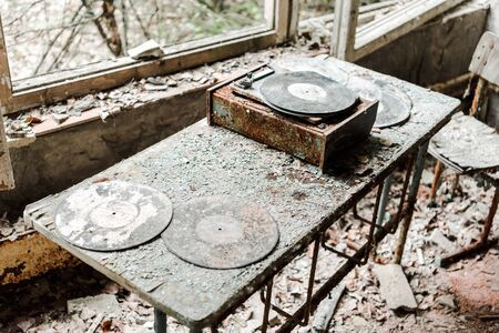 abandoned vinyl records on dirty table in room