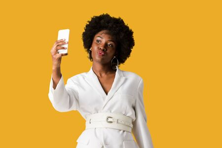 attractive african american woman with duck face taking selfie isolated on orange