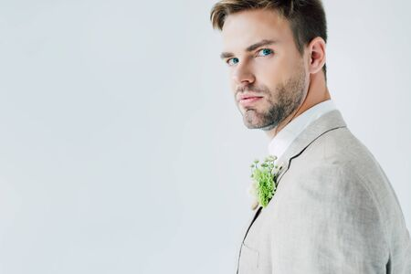 handsome bridegroom in suit with floral boutonniere looking at camera isolated on grey