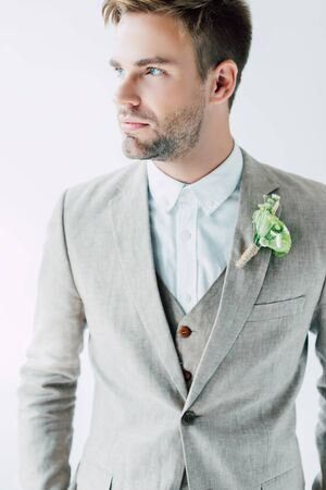 handsome bridegroom in suit with floral boutonniere looking away isolated on grey 版權商用圖片
