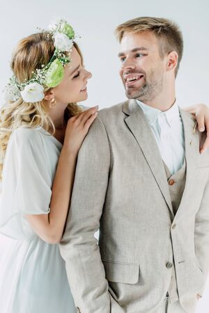 attractive bride and handsome bridegroom smiling and looking at each other isolated on grey