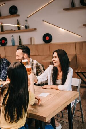 young friends clinking glasses of light beer while spending time together in pub