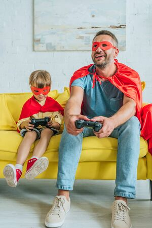 KYIV, UKRAINE - JULY 5, 2019: Cheerful father and son in costumes of superheroes sitting on sofa and playing video game