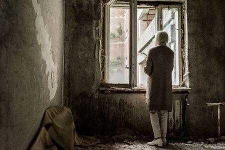 back view of retired woman holding plant in empty room near windows 版權商用圖片