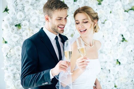 attractive bride and handsome bridegroom smiling and clinking with champagne glasses Stock Photo