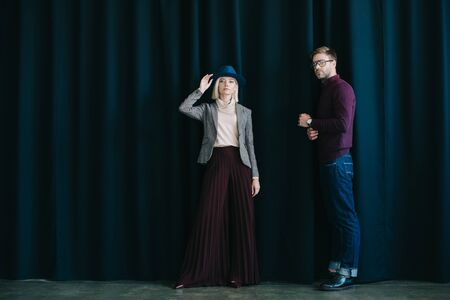 full length view of stylish young man in glasses and blonde woman in hat near curtain