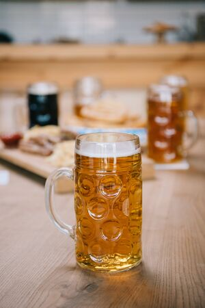 selective focus of mug with lager beer on wooden table in pub 写真素材
