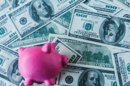 top view of pink piggy bank on dollar banknotes 版權商用圖片