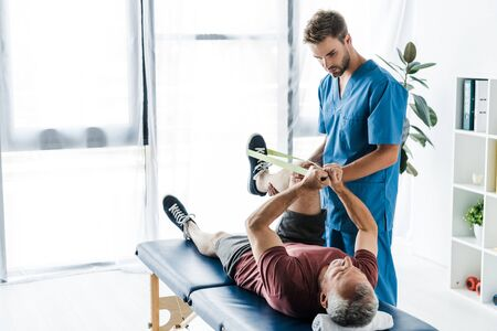 handsome bearded doctor holding leg of mature patient exercising with elastics