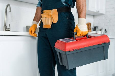 cropped view of worker in uniform standing and holding toolbox