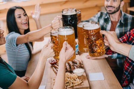 Amigos alegres tintineo de jarras de cerveza mientras celebraba en el pub octoberfest Foto de archivo