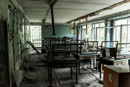 abandoned and creepy classroom with dirty tables in school