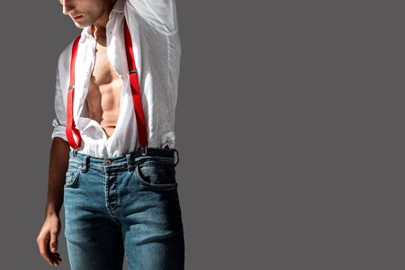 cropped view of man in white shirt and red suspenders isolated on grey
